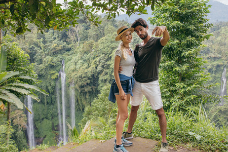 Beautiful couple together on cliff taking selfie with waterfall
