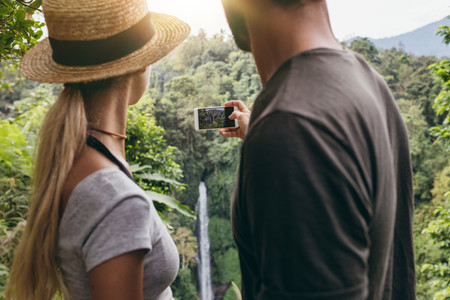 Young couple taking a picture of water fall