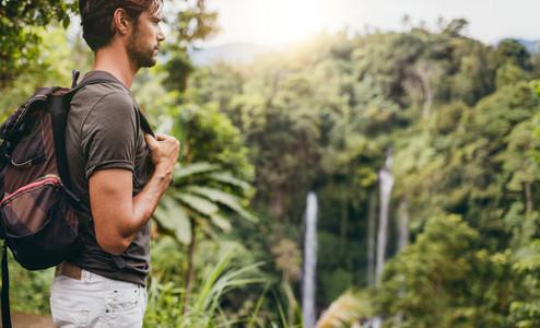 Man hiking near waterfall