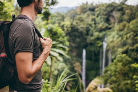 Male hiker near waterfall in forest