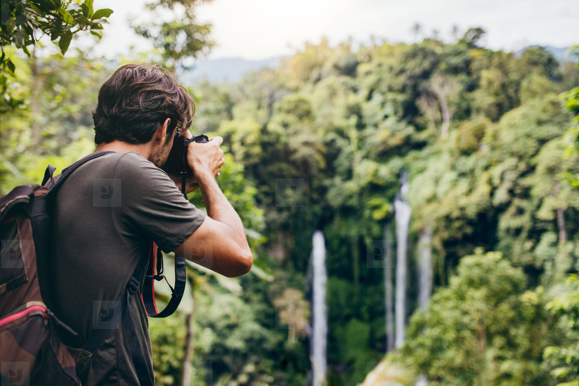 Male hiker photographing a waterfall in forest