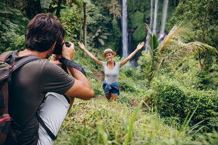 Photographer taking pictures of a woman by waterfall