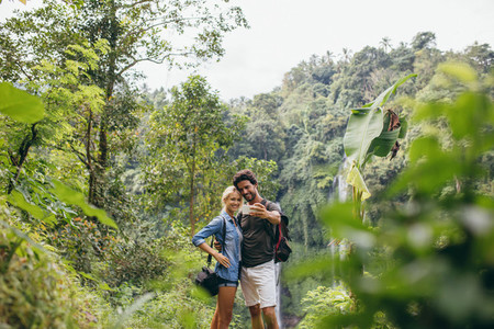 Young tourists taking selfie in the forest
