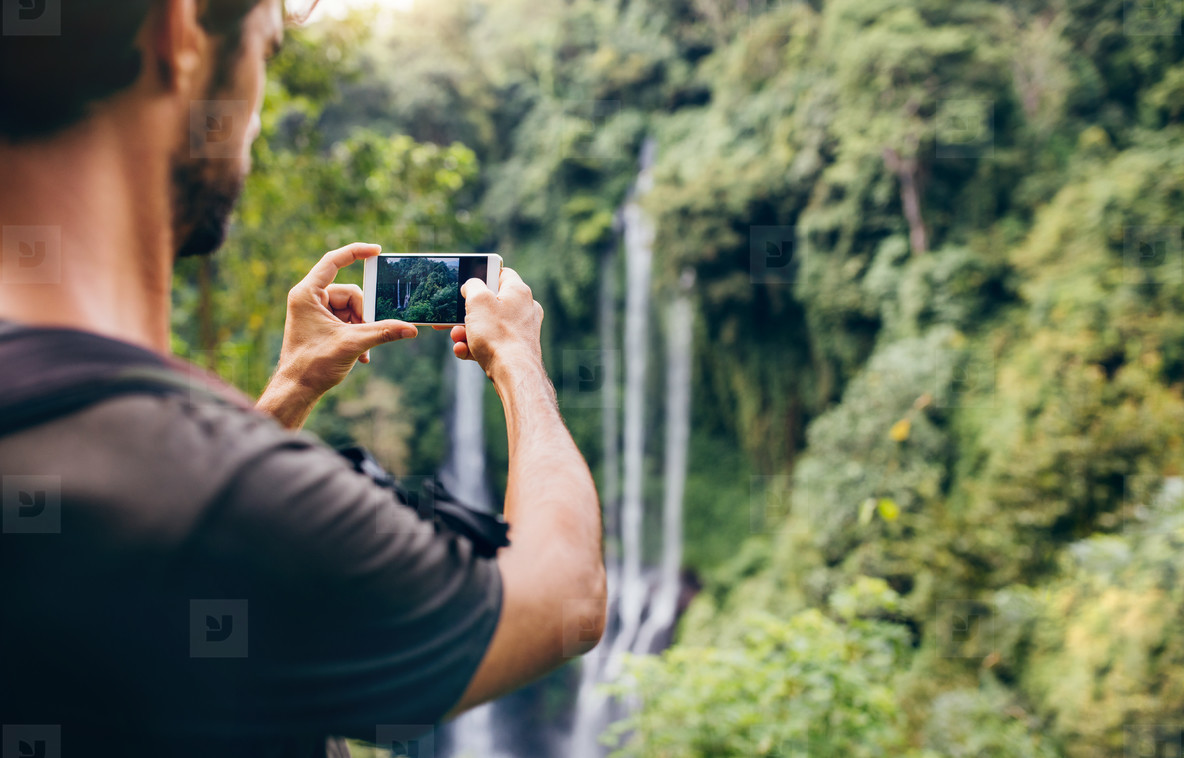 Man taking photos of waterfall with his cellphone