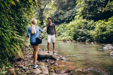Young couple walking by the mountain stream