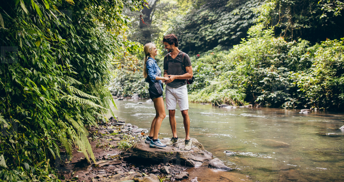 Loving young couple standing by mountain stream