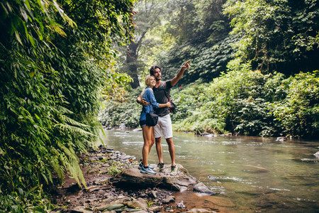 Hiking couple by stream looking at a view