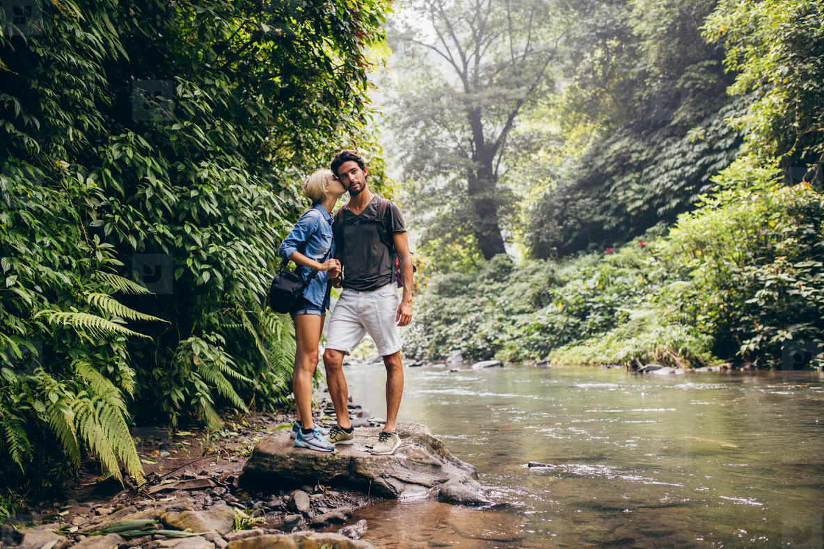 Loving couple standing by mountain stream