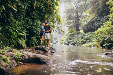 Young couple together by the creek and looking away