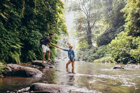 Young couple walking across stream