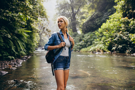 Beautiful woman with backpack standing by the creek