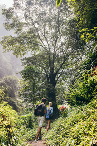 Couple of tourists walking along the forest trail