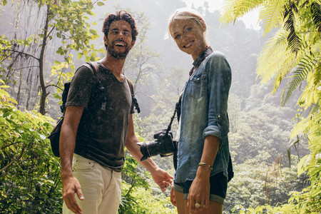 Hiker couple standing together during rain in the forest