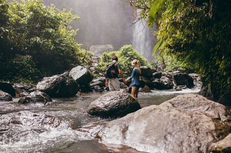 Young couple crossing stream in forest