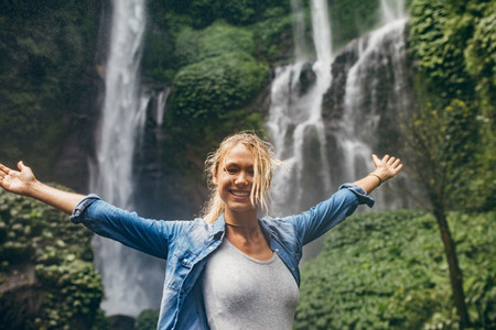 Tourist with tropical waterfall in background