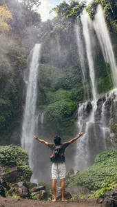 Male tourist enjoying near waterfall