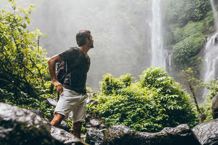 Male hiker near waterfall during rain