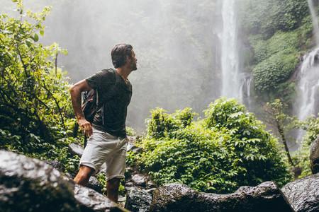 Male hiker near waterfall during rain
