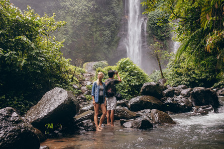 Young couple standing by the stream near the waterfall