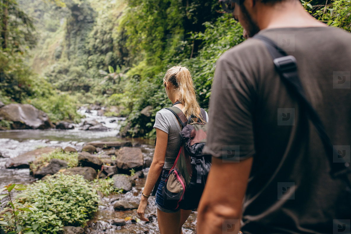 Tourist couple walking by stream