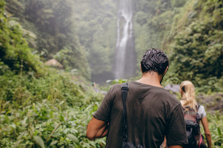 Couple of tourists walking towards a waterfall in forest
