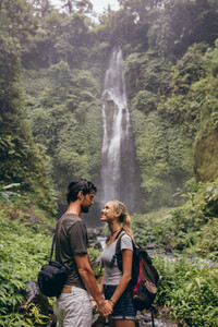 Couple in love standing near a waterfall in forest