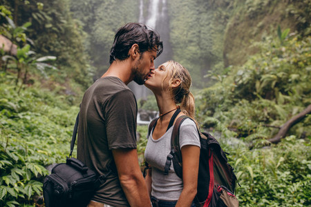 Loving young couple kissing while standing in the forest