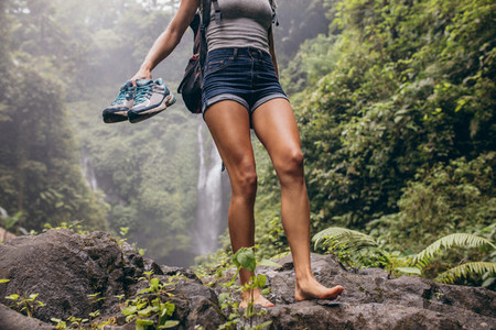 Woman hiking barefoot on forest trail
