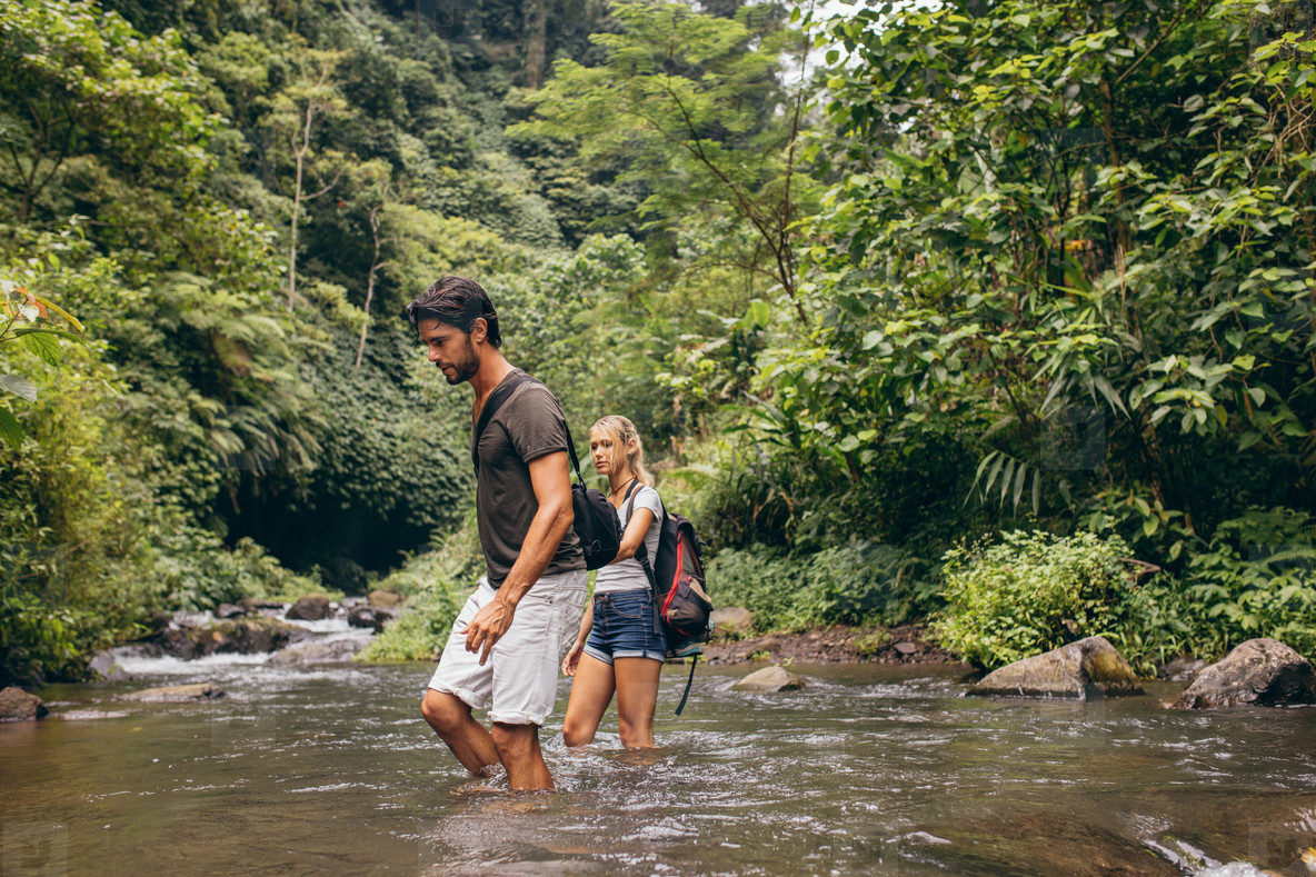 Couple crossing mountain stream