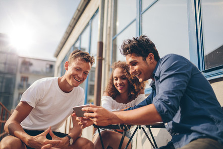 Group of friends watching video on smartphone