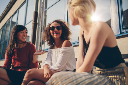 Three young women meeting at outdoor cafe