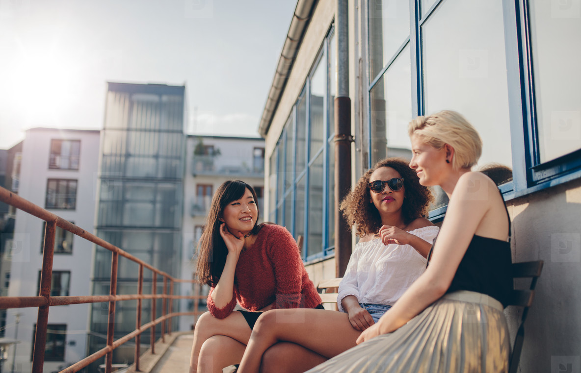 Three young female friends sitting in balcony