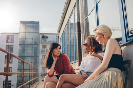 Three young women sitting outdoors and chatting