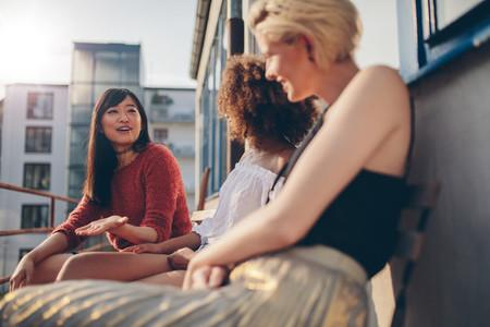 Multiracial women relaxing outdoors in a balcony