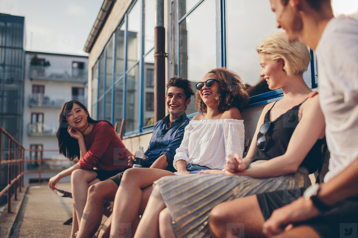 Multiracial group of friends sitting in balcony and smiling