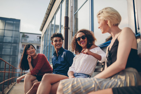Multiethnic group of friends in balcony and talking