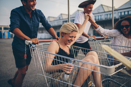 Young friends having fun on a shopping carts