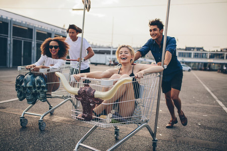 Young people racing with shopping trolleys