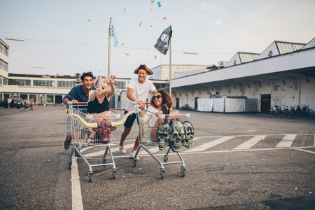 Young friends having fun on a shopping trolleys