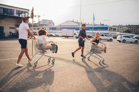 Young friends having fun on a shopping carts