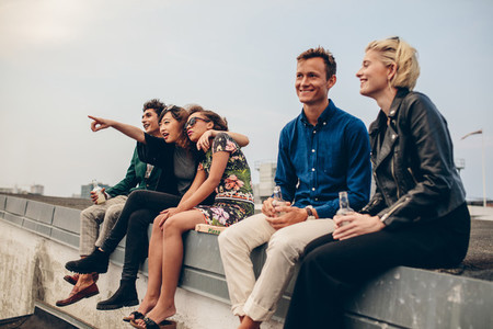 Happy young friends relaxing on rooftop