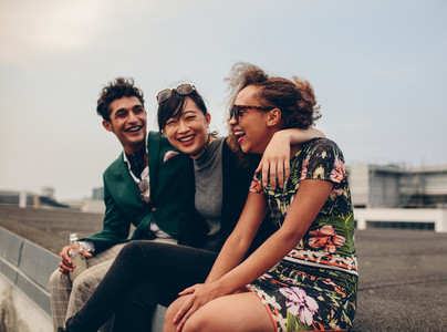 Friends laughing together on rooftop