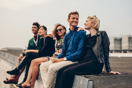 Men and women sitting together on rooftop