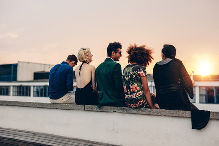 Young friends relaxing on terrace during sunset