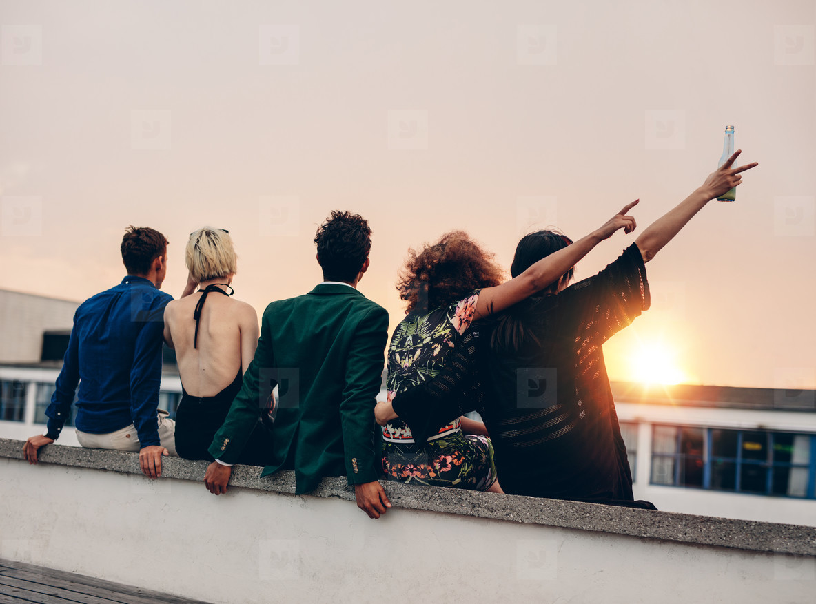 Friends enjoying drinks on rooftop at sunset
