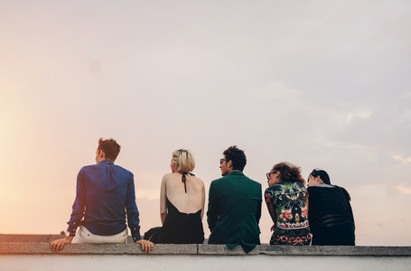 Young people hanging out on rooftop at sunset
