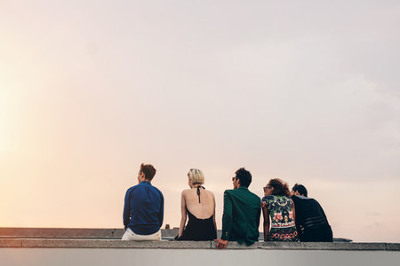 Friends sitting together on rooftop at sunset