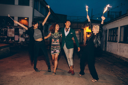 Group of friends enjoying with sparklers on road