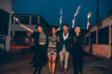 Friends enjoying nighttime party with sparklers in city