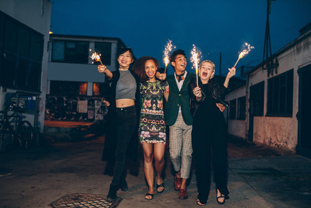 Group of friends walking with sparklers on road in evening